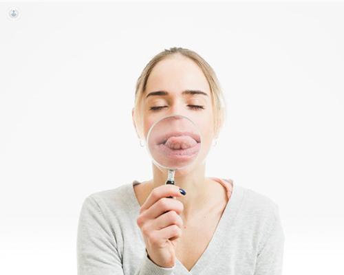 Chica mostrando la lengua, que está enfocada por una lupa - enfermedades de la lengua by Top Doctors