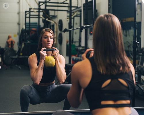 Chica cogiendo una pesa en el gimnasio - crossfit- entrenamiento de fuerza by Top Doctors